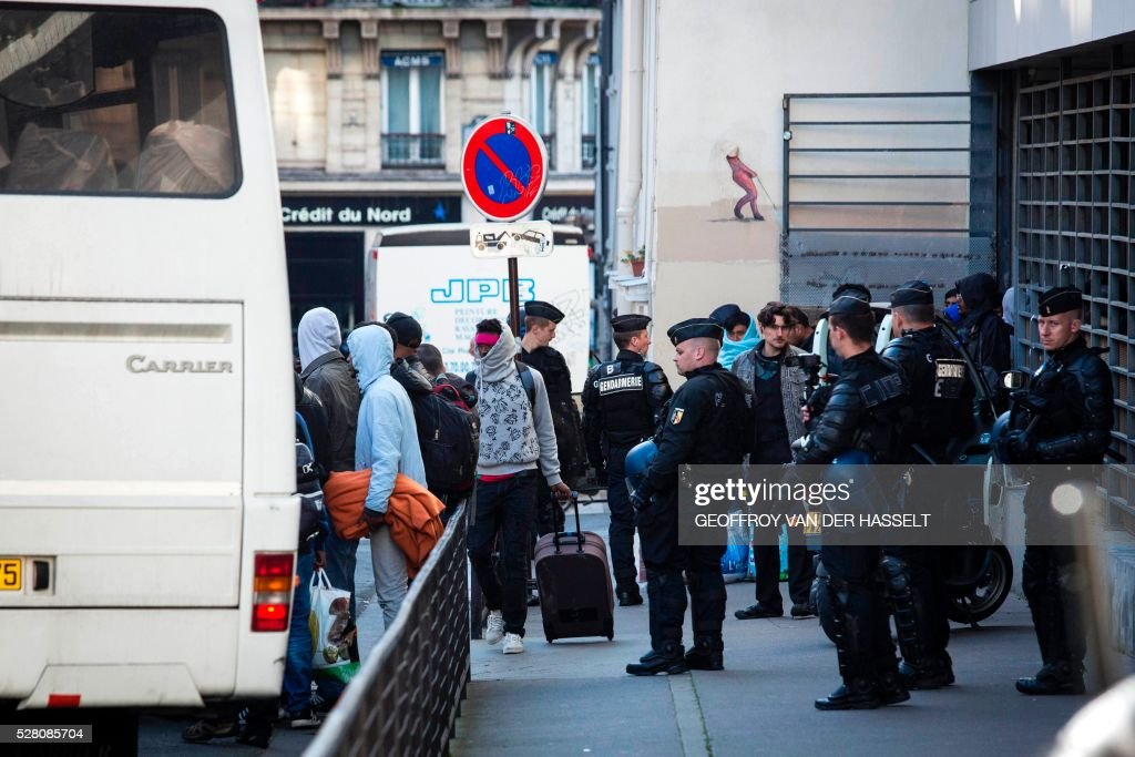 CORRECTION - Migrants evacuate an occupied highschool under the police supervision in Paris on May 4, 2016. A highschool under construction occupied by 200 migrants in northeatern Paris since two weeks has been evacuated this morning by the police, while protesters clashed with policemen outside the building. / AFP / GEOFFROY VAN DER HASSELT / The erroneous mention[s] appearing in the metadata of this photo by GEOFFROY VAN DER HASSELT has been modified in AFP systems in the following manner: [Migrants evacuate an occupied highschool under the police supervision in Paris on May 4, 2016] instead of [A woman raises a baby bottle as migrants evacuate an occupied highschool under the police supervision in Paris on May 4, 2016]. Please immediately remove the erroneous mention[s] from all your online services and delete it (them) from your servers. If you have been authorized by AFP to distribute it (them) to third parties, please ensure that the same actions are carried out by them. Failure to promptly comply with these instructions will entail liability on your part for any continued or post notification usage. Therefore we thank you very much for all your attention and prompt action. We are sorry for the inconvenience this notification may cause and remain at your disposal for any further information you may require.