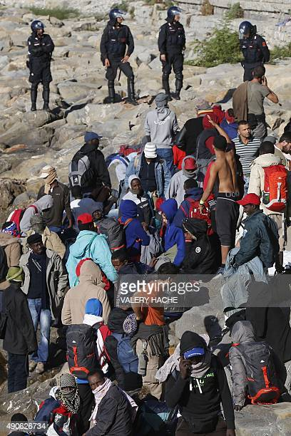 Migrants face Italian police officers on the rocks on the shoreline on September 30 2015 at the FrenchItalian border in Ventimiglia The camp of...