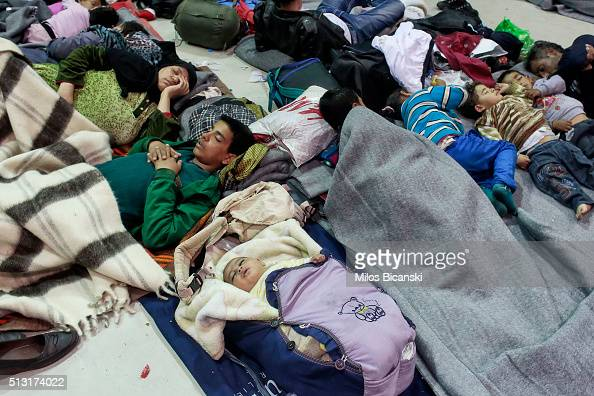 Migrants find shelter in the passenger terminal after arriving from the islands at the port of Piraeus on February 29 2016 in Athens Greece Border...