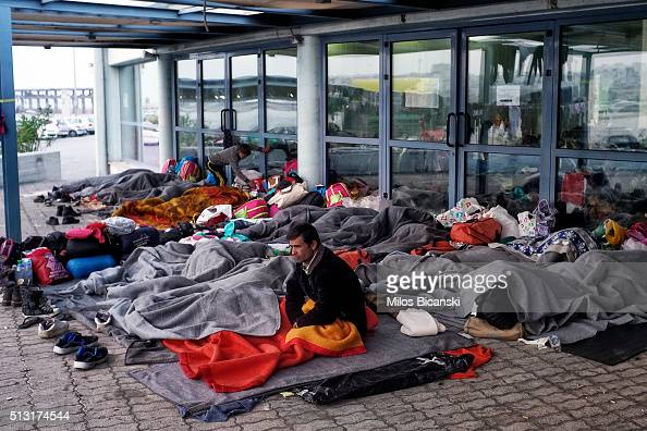 Migrants find shelter outside the passenger terminal after arriving from the islands at the port of Piraeus on March 1 2016 in Athens Greece Border...