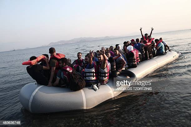 Migrants flash the 'V for Victory' sign as they arrive in a boat on a beach on the Greek island of Kos after crossing a part of the Aegean Sea...