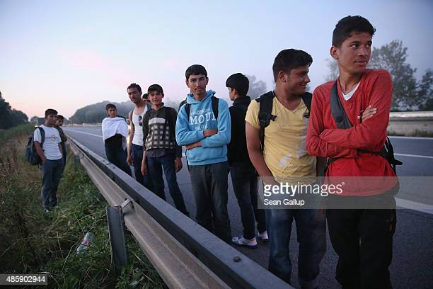 Migrants from Afghanistan detained by police stand along the A3 highway shortly after they crossed from Austria into Germany in the early hours on...