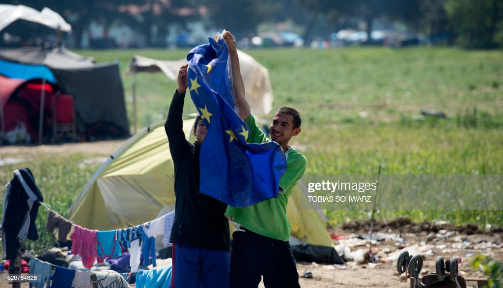 Migrants from Afghanistan present an EU flag they found at their tent at a makeshift camp for migrants and refugees near the village of Idomeni not far from the Greek-Macedonian border on May 1, 2016. Some 54,000 people, many of them fleeing the war in Syria, have been stranded on Greek territory since the closure of the migrant route through the Balkans in February. / AFP / TOBIAS
