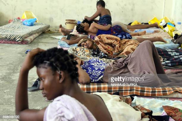 TOPSHOT Migrants from African origin rest in a room at the Interior ministry's alNasr housing center for illegal immigrants on August 31 2016 in the...