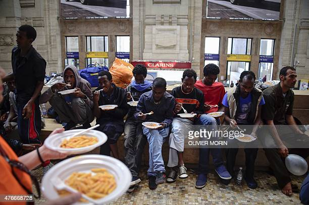 Migrants from Eritrea eat a meal they received at the Milan train station on June 11 as about 300 migrants arrived in Milan late on June 10 and wait...