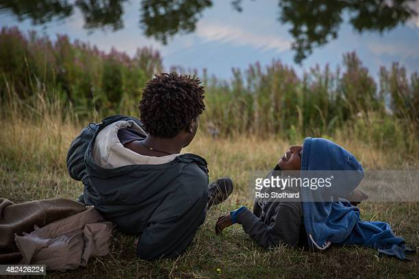 Migrants from Eritrea sit beside a lake near the Eurotunnel terminal in Coquelles on July 30 2015 in Calais France Hundreds of migrants are...