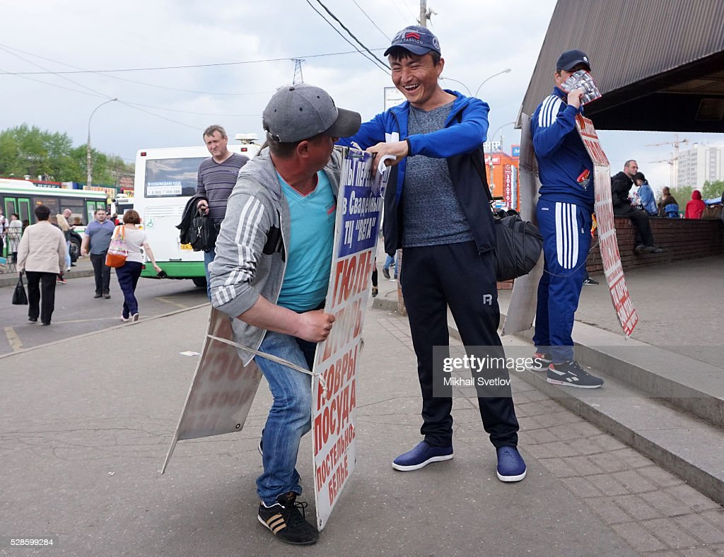 Migrants from Kyrgyzstan hold advirtising banners to promote a china shop at the street market in Central Moscow on May,4,2016 in Sochi, Russia. Russia's anticipated economic recovery has been delayed, and the country continues to adjust to an adverse external environment of lower oil prices and international sanctions. In 2015, the consequences of these twin shocks caused real GDP to contract 3.7 percent, the World Bank said in its latest Russia Economic Report launched in Moscow today.