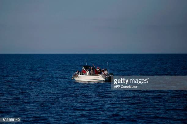 Migrants from Libya wave from a boat as they wait to be rescued by the Aquarius rescue ship run by NGO SOS Mediterranee and Medecins Sans Frontieres...