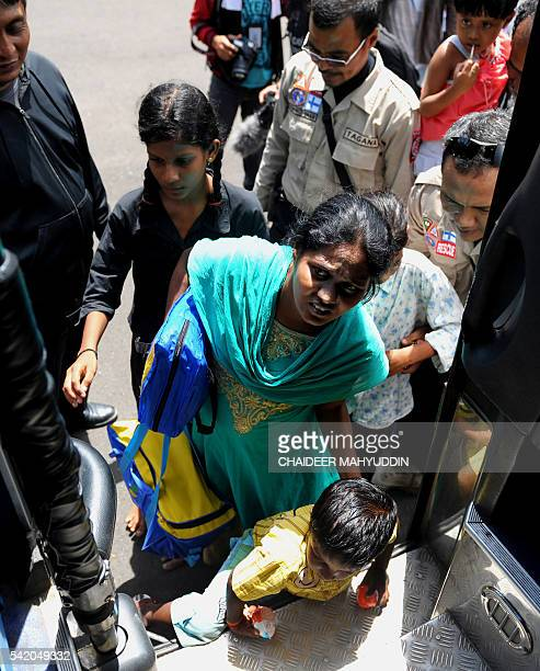 Migrants from Sri Lanka who were stranded on a boat on the west coast of Sumatra island for over a week board a bus in Lhoknga in Aceh province on...