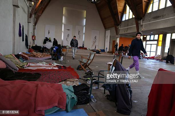 Migrants from Syria and Afghan walk in a former church where sixty migrants live on March 3 2016 in CherbourgOcteville northwestern France The...