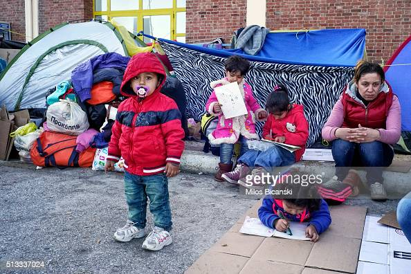 Migrants from Syria in front of an improvised shelter outside a passenger terminal at the port of Piraeus on March 2 2016 in Athens Greece Border...