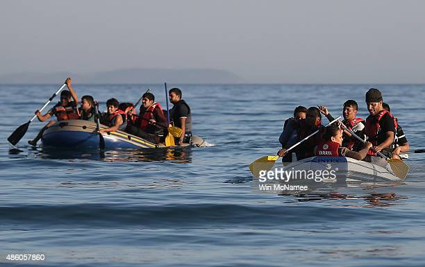 Migrants from Syria paddle toward shore while completing a journey in a small dinghy crossing a three mile stretch of the Aegean Sea from Turkey...