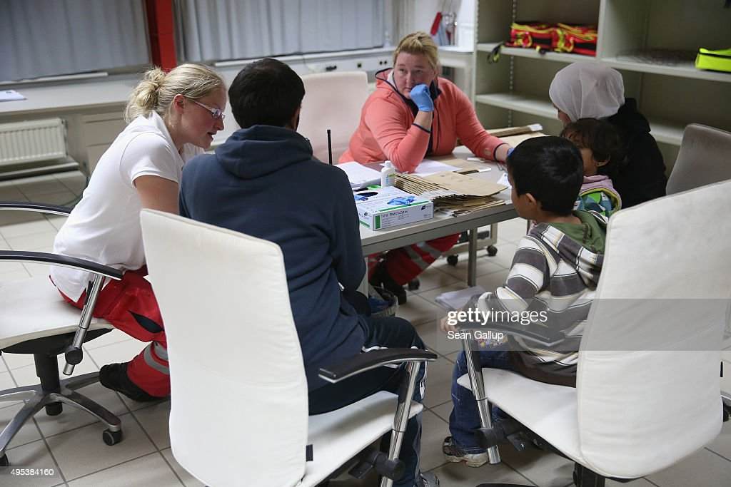 Migrants from Syria seeking asylum in Germany undergo a brief medical evaluation upon their arrival at a former office park that has become short-term accommodation for migrants on November 2, 2015 in Sumte, Germany. Sumte, a farming village located southwest of Hamburg with a population of 102, has begun receiving 500 migrants who are being housed in an abandoned office park on the village edge. The number of migrants at the shelter could reach up to 750 in coming weeks as Germany struggles to accommodate the unrelenting flood of migrants arriving at a rate of thousands per day. Authorities are distributing migrants seeking asylum in Germany at shelters nationwide, both in urban centers and in small, rural communities.