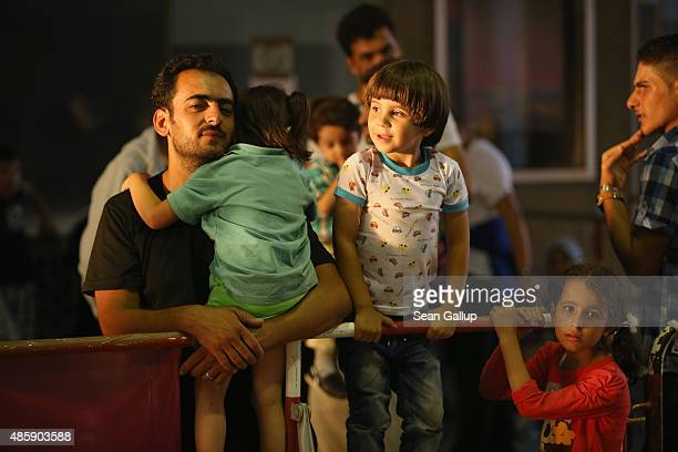 Migrants from Syria stand in a holding area after arriving at Munich Hauptbahnhof main railway station and being detained by police on August 29 2015...