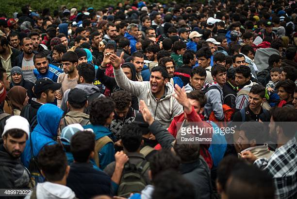 Migrants from Syria try to organise the queue as they wait to cross into Croatia through the Serbian border on September 25 2015 in Bapska Croatia...