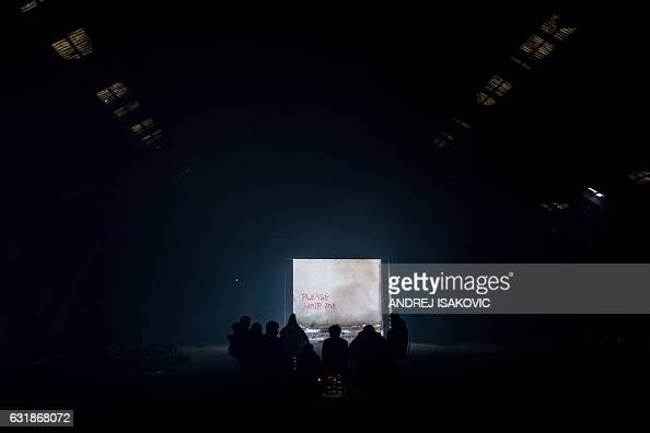 TOPSHOT Migrants gather around a bonfire inside of derelict warehouse used as a shelter near Belgrade's main railway station on January 17 with...