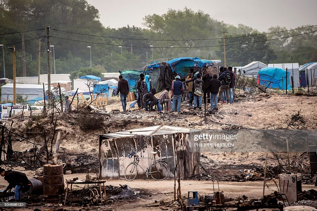 Migrants gather in the middle of burnt tents after a massive brawl that left 40 people injured in the 'Jungle' migrant camp in the northern French town of Calais on May 27, 2016. Some 20 people living in the 'Jungle' refugee camp in the northern French port of Calais were injured in a brawl between around 200 Afghans and Sudanese on May 26, 2016. / AFP / PHILIPPE