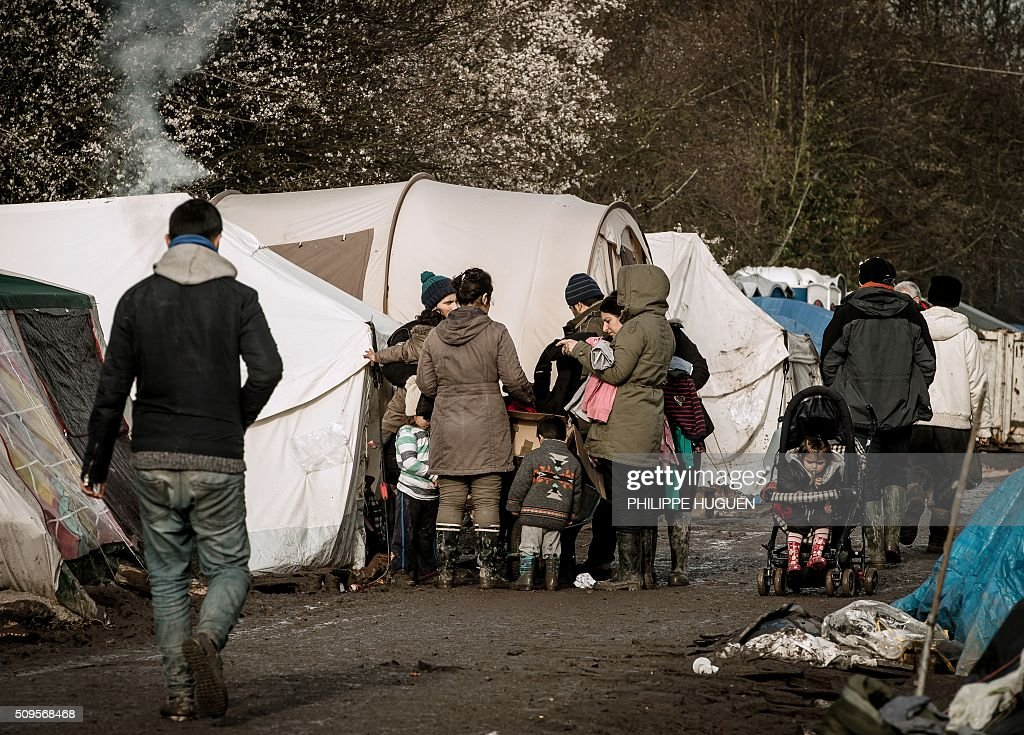 Migrants gather in the so-called 'Jungle' migrant camp in Gande-Synthe where 2,500 refugees from Kurdistan, Iraq and Syria live on February 11, 2016 in Grande-Synthe near the city of Dunkirk, northern France. / AFP / PHILIPPE HUGUEN