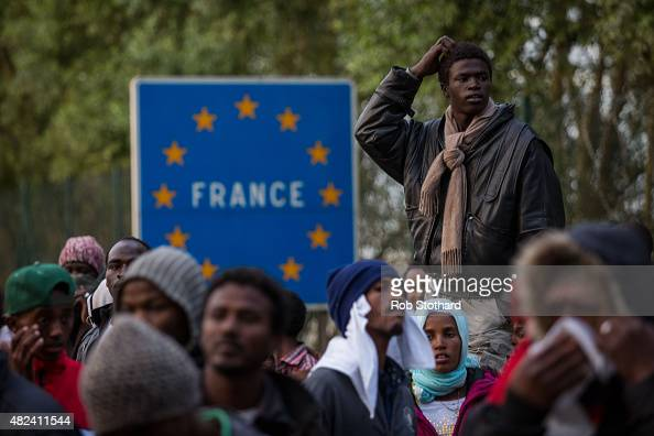 Migrants gather near the Eurotunnel terminal in Coquelles on July 30 2015 in Calais France Hundreds of migrants are continuing to attempt to enter...