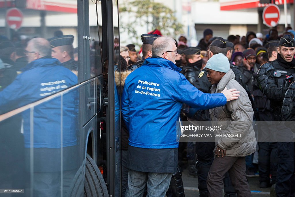 Migrants get on a bus to be transferred to reception centres, after being evacuated by French police officers and gendarmes from a makeshift camp under the Stalingrad metro station in Paris, on May 2, 2016. / AFP / Geoffroy Van der Hasselt