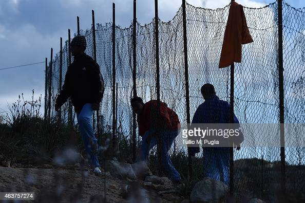 Migrants go through a hole of the external fence of the Temporary Permanence Centre on February 18 2015 in Lampedusa Italy Hundreds of migrants have...