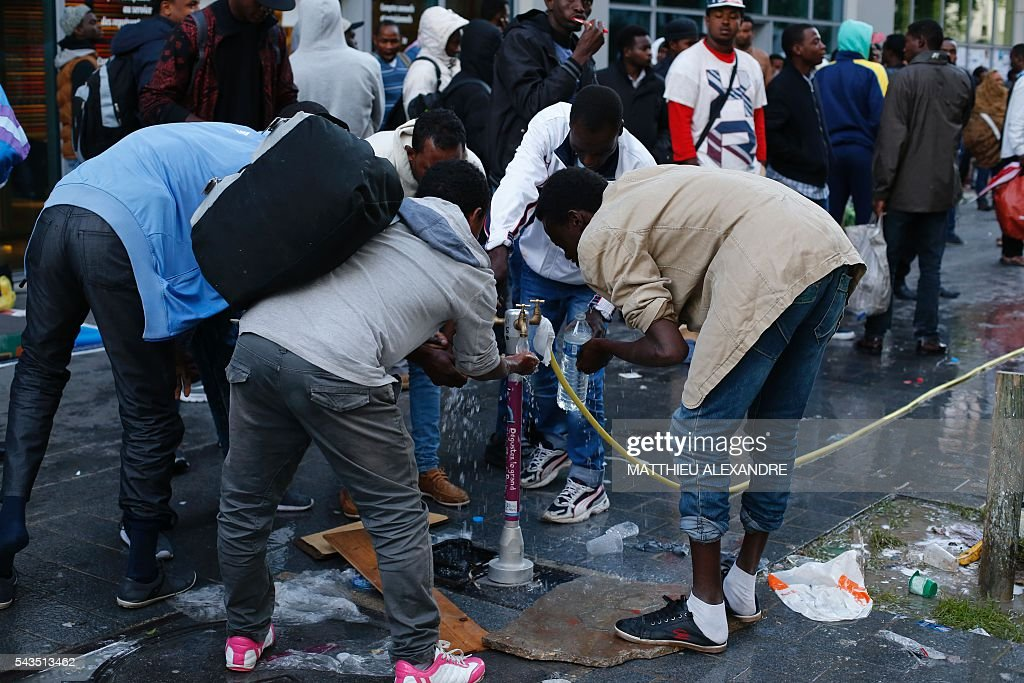 Migrants groom at wake-up as they wait for the French Gendarmes to evacuate their camp on June 29, 2016 in Paris. The police started early on June 29, 2016, the evacuation of several hundreds of migrants, from a camp at the former SNCF Hall 'Pajol'. / AFP / MATTHIEU