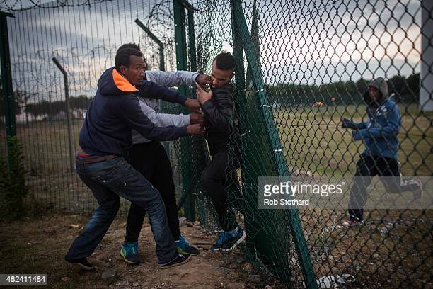 Migrants help a man squeeze through a gap in a fence near the Eurotunnel terminal in Coquelles on July 30 2015 in Calais France Hundreds of migrants...