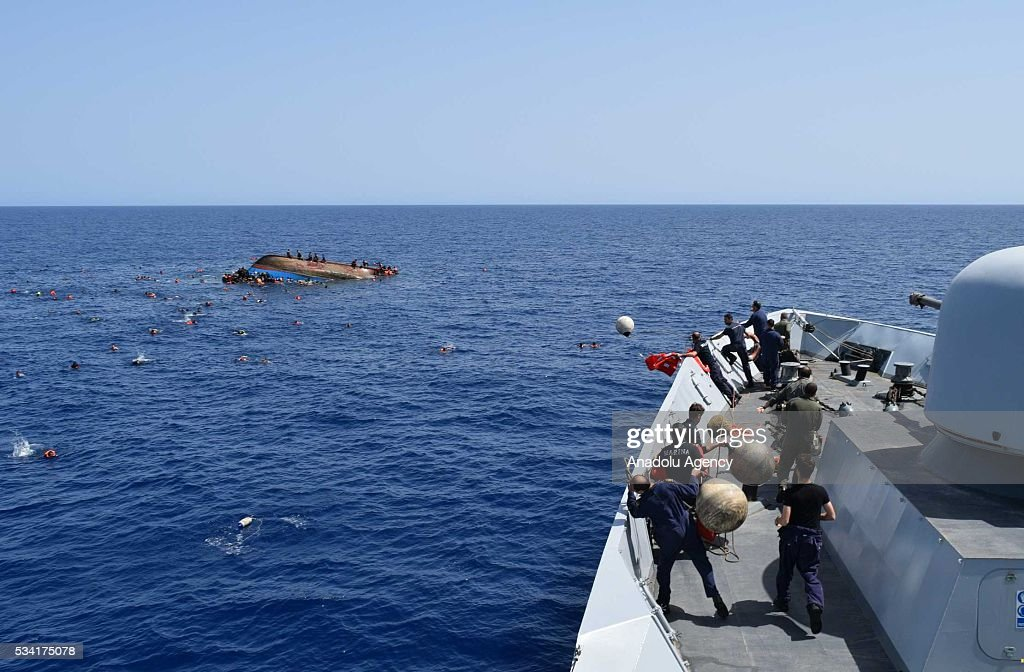 Migrants in a capsized boat are rescued by Bettica and Bergamini ships of Italian Navy at Sicilian Strait, between Libya and Italy, in Mediterranean sea on May 25, 2016. The Italian Navy saved around 500 migrants as they found dead bodies of seven migrants in the sea during the operations.