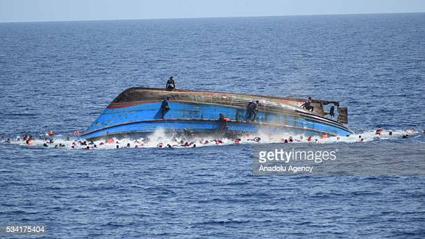 Migrants in a capsized boat are rescued by Bettica and Bergamini ships of Italian Navy at Sicilian Strait between Libya and Italy in Mediterranean...