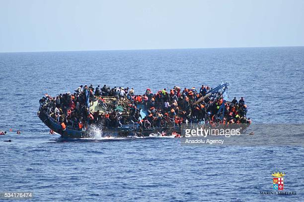 Migrants in an overcrowded boat which was about to capsize are rescued by Bettica and Bergamini ships of Italian Navy at Sicilian Strait between...