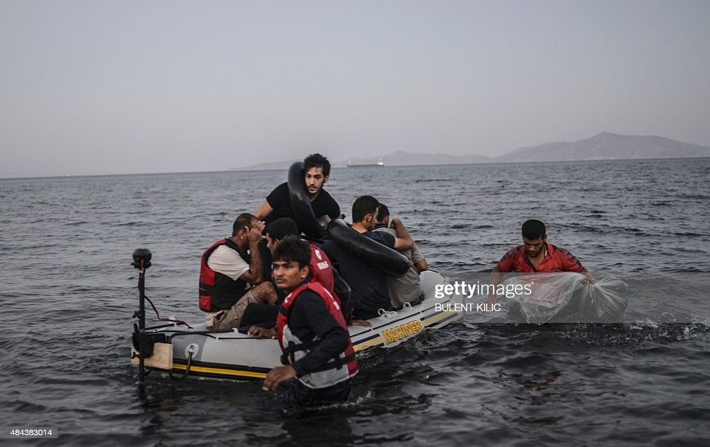 Migrants leave aboard a boat to the Greek island of Kos on early August 18, 2015 off the shore of Bodrum, southwest Turkey. Authorities on the island of Kos have been so overwhelmed that the government sent a ferry to serve as a temporary centre to issue travel documents to Syrian refugees -- among some 7,000 migrants stranded on the island of about 30,000 people. The early hours are the safest time for migrants travelling from Turkey to the Greek islands just across the water, which have seen a huge influx of refugees escaping the civil war in Syria and chaos in Afghanistan since the beginning of this year.