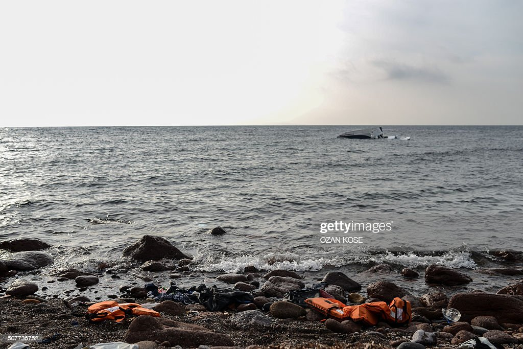 TOPSHOT Migrants' life vests are pictured on the beach as a boat that capsized is seen behind on January 31 2016 in Canakkale's Bademli district...
