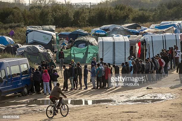Migrants line up for food distribution in the 'Jungle' migrants camp in the northern French city of Calais on October 29 2015 Winter is coming to...