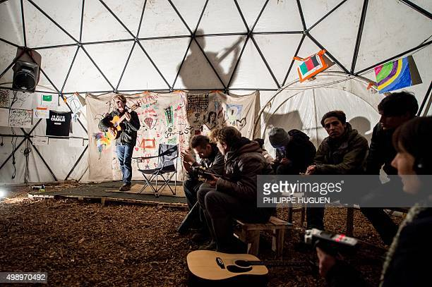 Migrants listen to a guitarist performing in a makeshift theatre on November 25 in the socalled 'Jungle' migrant camp in Calais northern France AFP...