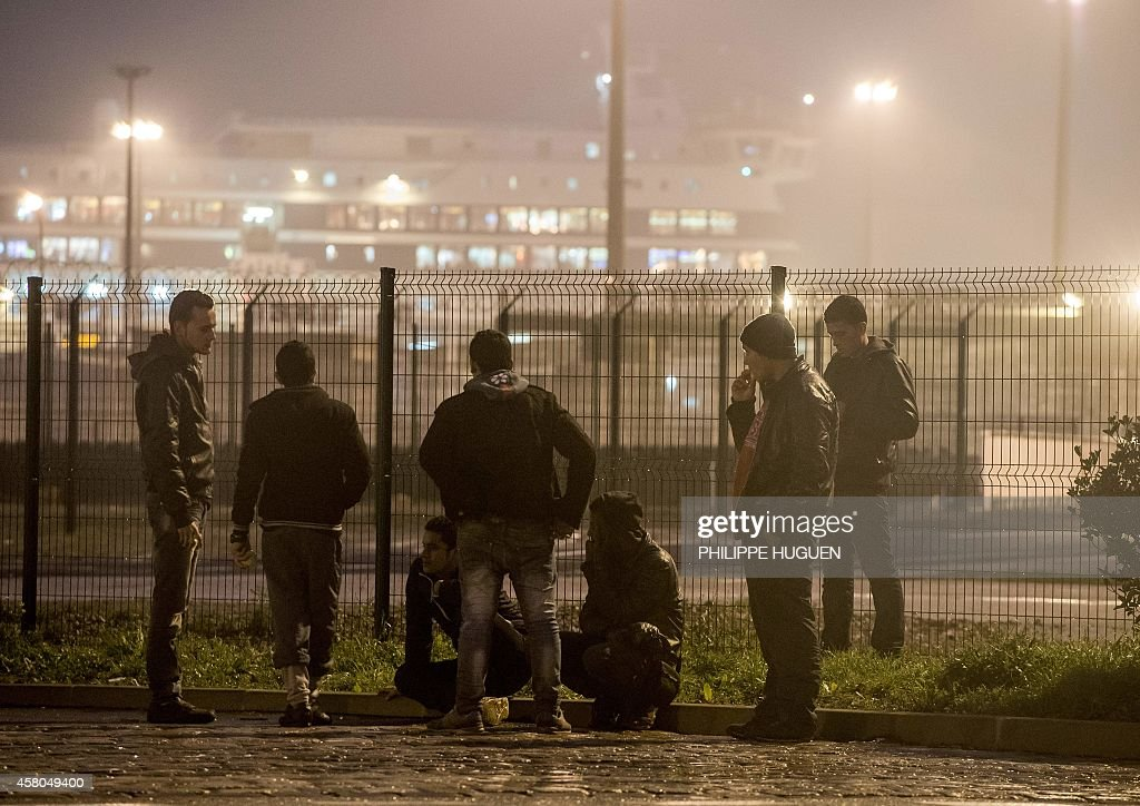 Migrants look at a car ferry in the northeastern French port of Calais on October 29 2014 The mayor of Calais told lawmakers in London on October 28...