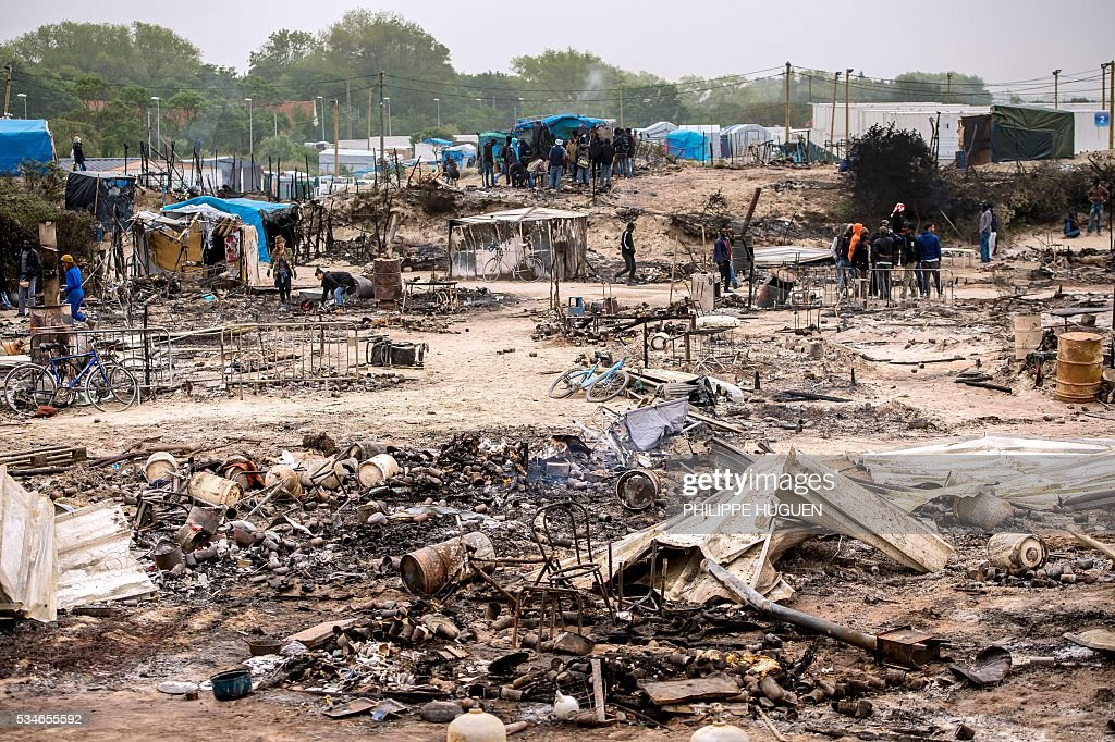 Migrants look at the burnt tents after a massive brawl that left 40 people injured in the 'Jungle' migrant camp in the northern French town of Calais on May 27, 2016. Some 20 people living in the 'Jungle' refugee camp in the northern French port of Calais were injured in a brawl between around 200 Afghans and Sudanese on May 26, 2016. / AFP / PHILIPPE
