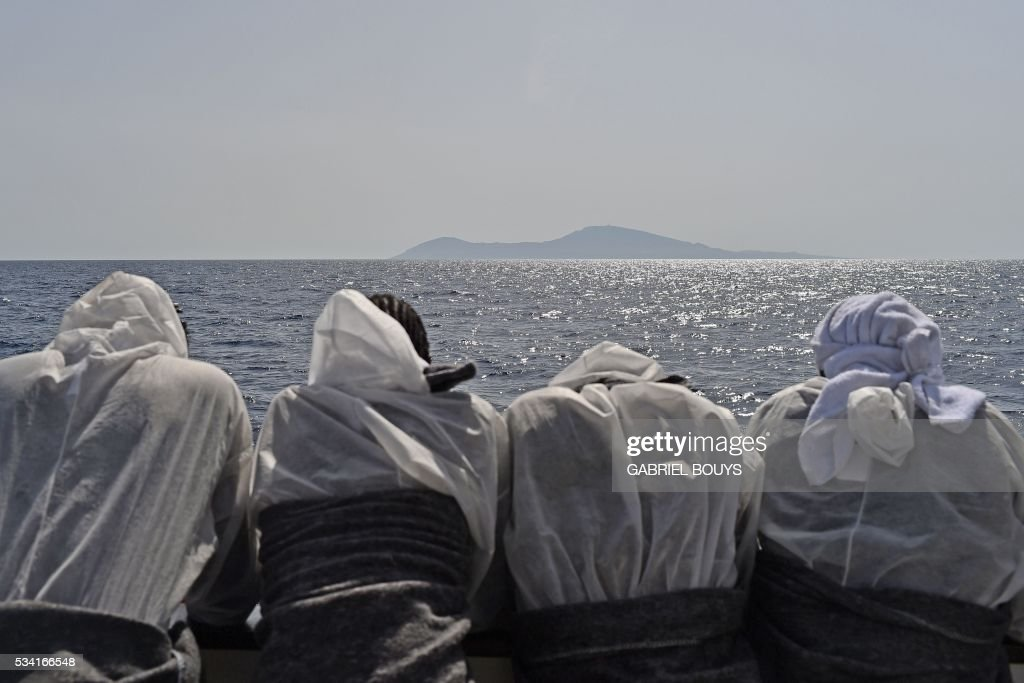 Migrants look at the Pantelleria island from the rescue ship 'Aquarius', on May 25, 2016 a day after a rescue operation of migrants and refugees off the Libyan coast. The Aquarius is a former North Atlantic fisheries protection ship now used by humanitarians SOS Mediterranee and Medecins Sans Frontieres (Doctors without Borders) which patrols to rescue migrants and refugees trying to reach Europe crossing the Mediterranean sea aboard rubber boats or old fishing boat. / AFP / GABRIEL