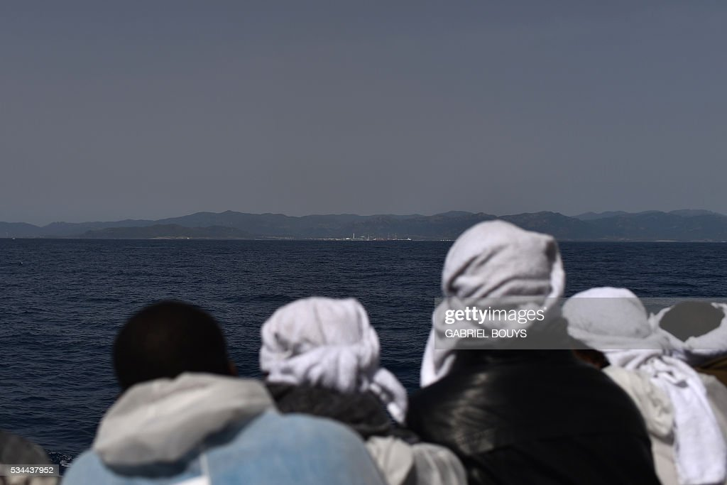 Migrants look at the Sardinia island from rescue ship 'Aquarius' prior to arrive in the port of Cagliari, on May 26, 2016, two days after being rescued near the Libyan coasts. The Aquarius is a former North Atlantic fisheries protection ship now used by humanitarians SOS Mediterranee and Medecins Sans Frontieres (Doctors without Borders) which patrols to rescue migrants and refugees trying to reach Europe crossing the Mediterranean sea aboard rubber boats or old fishing boat. / AFP / GABRIEL