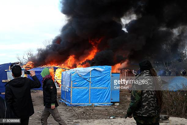 Migrants look on as a hut burns as police officers clear part of the 'jungle' migrant camp on February 29 2016 in Calais France The French...