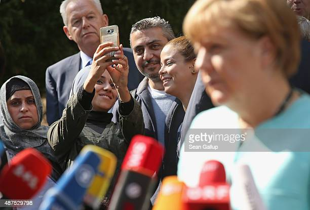 Migrants look on as German Chancellor Angela Merkel speaks to the media after she visited the AWO Refugium Askanierring shelter for migrants on...