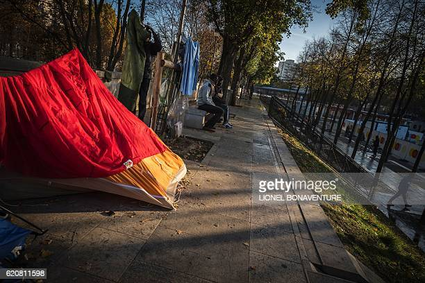 Migrants look on on November 3 2016 in Paris at a migrant tent camp at the Stalingrad metro station one of several camps sprouting up around the...