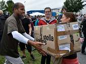 Migrants look through the donation boxes as locals gather with migrants seeking asylum in Germany for a welcome fest at the migrants shelter on...