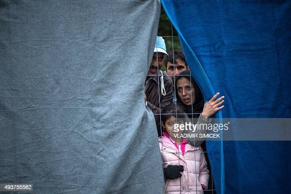 Migrants look through the fence as they wait to cross the SloveniaAustrian border in Spielfeld Austria on October 22 2015 Some thousands of people...