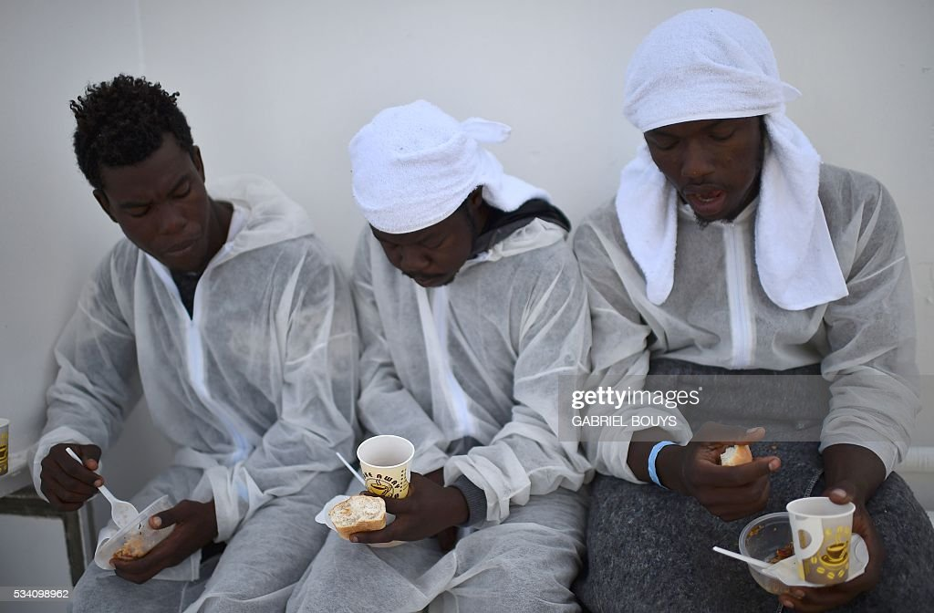 Migrants lunch aboard the rescue ship 'Aquarius', on May 25, 2016 a day after a rescue operation off the Libyan coast. The Aquarius is a former North Atlantic fisheries protection ship now used by humanitarians SOS Mediterranee and Medecins Sans Frontieres (Doctors without Borders) which patrols to rescue migrants and refugees trying to reach Europe crossing the Mediterranean sea aboard rubber boats or old fishing boat. / AFP / GABRIEL