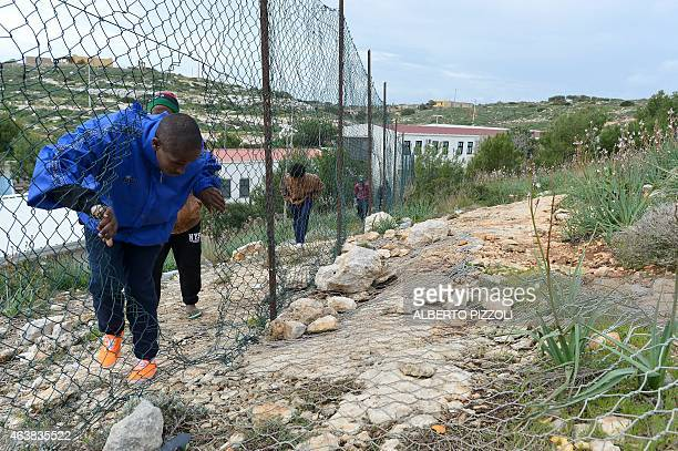 Migrants make a walk outside the 'Temporary Permanence Centre' a refugee camp on the Lampedusa island on February 19 2015 Authorities on the Italian...