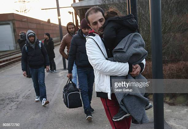 Migrants many of them from Syria walk to police vans after police found them while checking the identity papers of passengers on a train arriving...