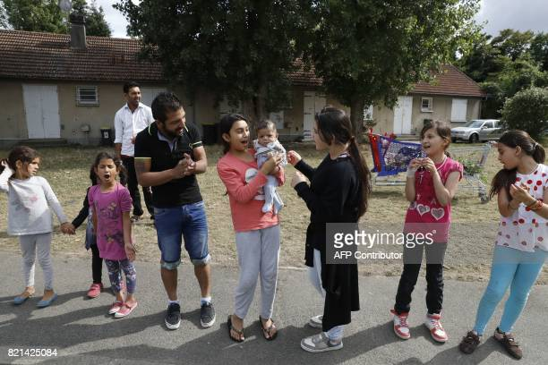 Migrants most of them from Syria form a human chain on July 20 2017 to protest a pending eviction from the former Cite de l'Air housing estate that...