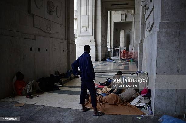 Migrants mostly from Eritrea rest at the Milan train station on June 13 as hundreds migrants arrived in Milan late on June 10 and wait to be taken...