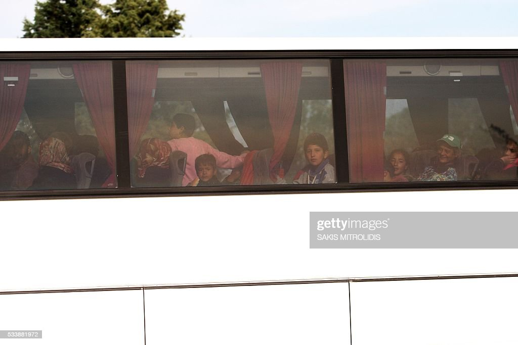 Migrants on a bus are evacuated from the makeshift camp at the Greek-Makedonian border near the village of Idomeni on May 24, 2016. In an operation which began shortly after sunrise on May 24, hundreds of Greek police began evacuating the sprawling camp which is currently home to 8,400 refugees and migrants, among them many families with children, an AFP correspondent said. At its height, there were more than 12,000 people crammed into the site, many of them fleeing war, persecution and poverty in the Middle East and Asia, with the camp exploding in size since Balkan states began closing their borders in mid February in a bid to stem the human tide seeking passage to northern Europe. / AFP / SAKIS