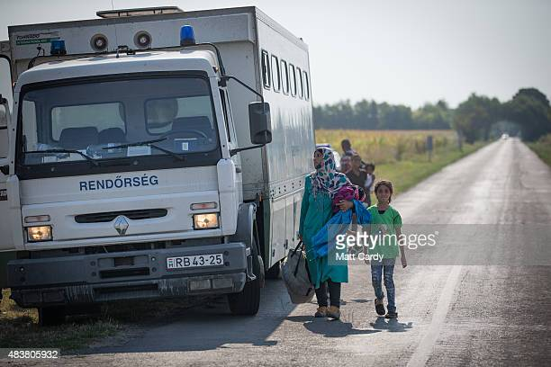 Migrants pass a police lorry as they walk down a road close to the border with Serbia and Hungary which they have just crossed on August 13 2015 near...